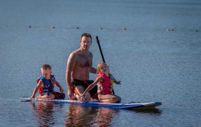 Dad with son and daughter on paddle board
