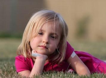serious little girl in grass
