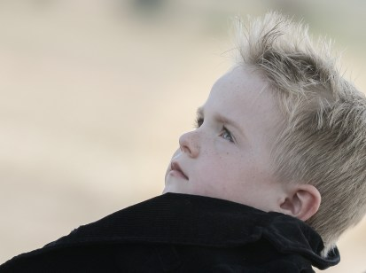 serious little boy black coat