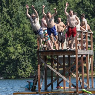 men jumping off raised dock
