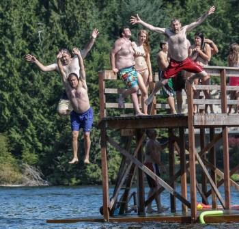 men doing a high jump into water