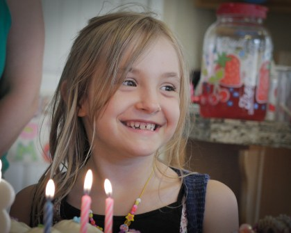 smiling girl behind birthday cake