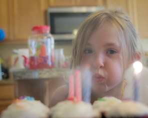 girl blowing out candles