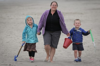 mom with son and daughter holding hands on beach