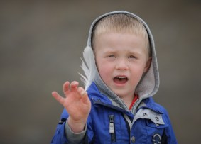 little boy with feather in hand