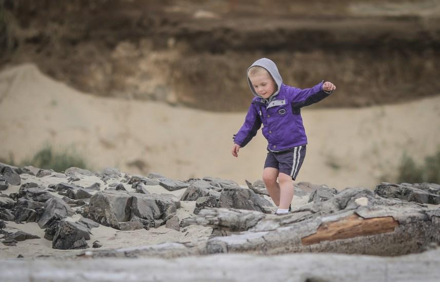boy walking on rocks