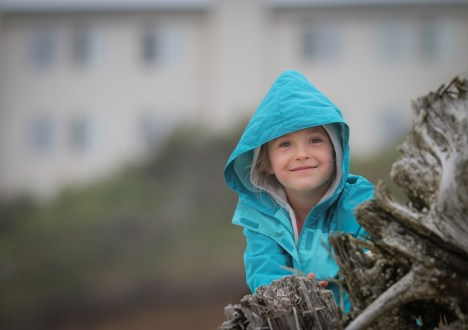 little smiling girl with hood on beach