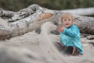 throwing sand looks like magic - little girl on beach