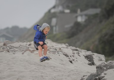 little boy in blue coat jumping on beach