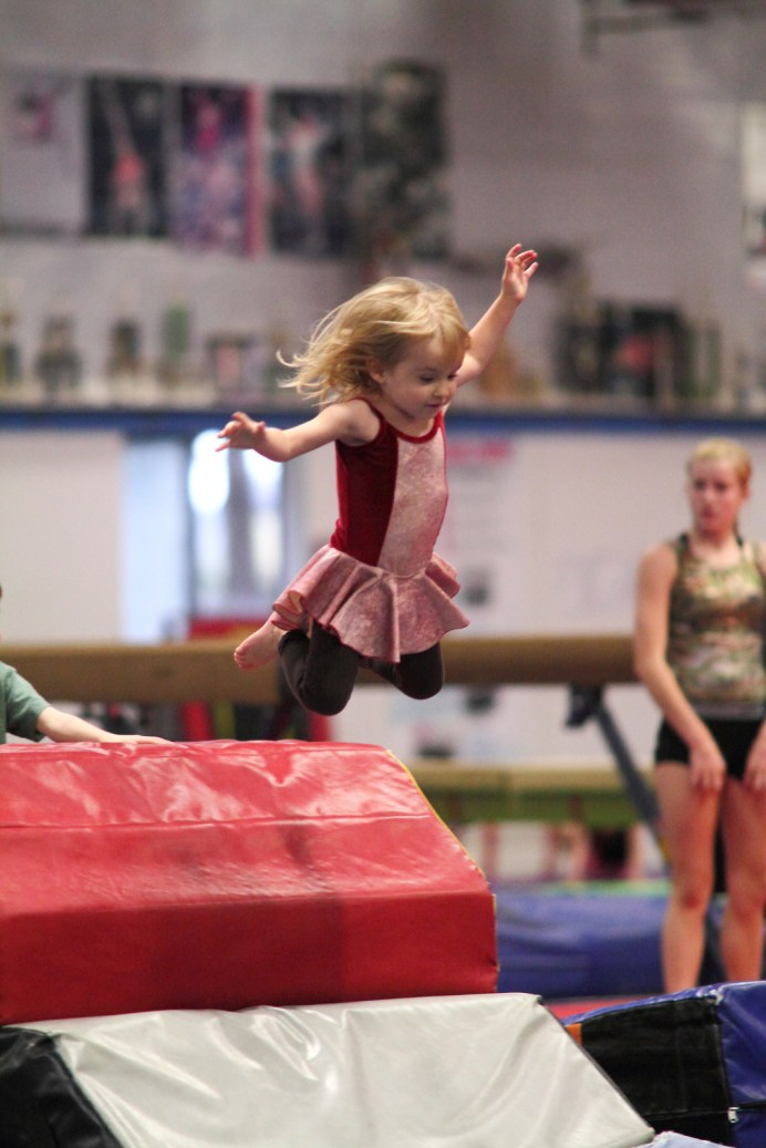 little girl airborne in gymnastics