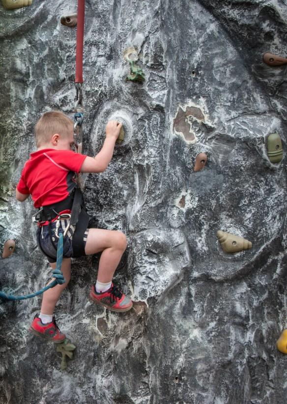 little boy climbing rock wall
