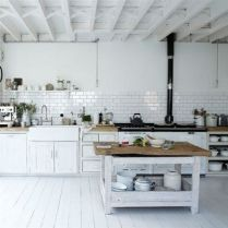The wooden chopping block adds warmth to an otherwise all white kitchen.