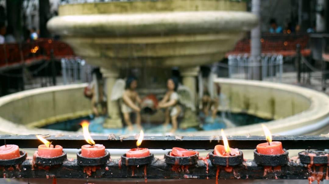 Devotees light candles in prayer at the basilica. (USJR MassCom intern Nel Mozol)