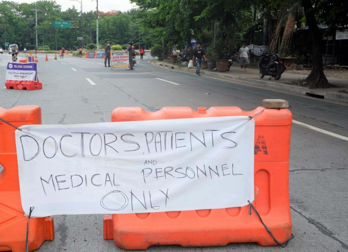 FRONTLINERS ONLY.  Authorities monitor those entering East Avenue from the Elliptical Road to BIR road in Quezon City, where there are several major hospitals. Only doctors, medical personnel, and patients are given the priority to access the area. (PNA photo by Robert Oswald P. Alfiler)