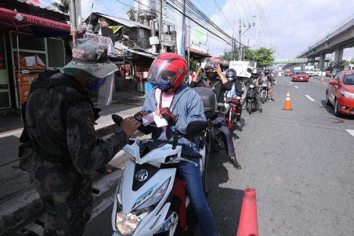 INSPECTION. A police officer inspects IDs and other documents presented by motorcycle riders entering Antipolo City, Rizal. Checkpoints remain despite easing of some restrictions under the general community quarantine which took effect in the province on May 16. (PNA photo by Joey O. Razon)