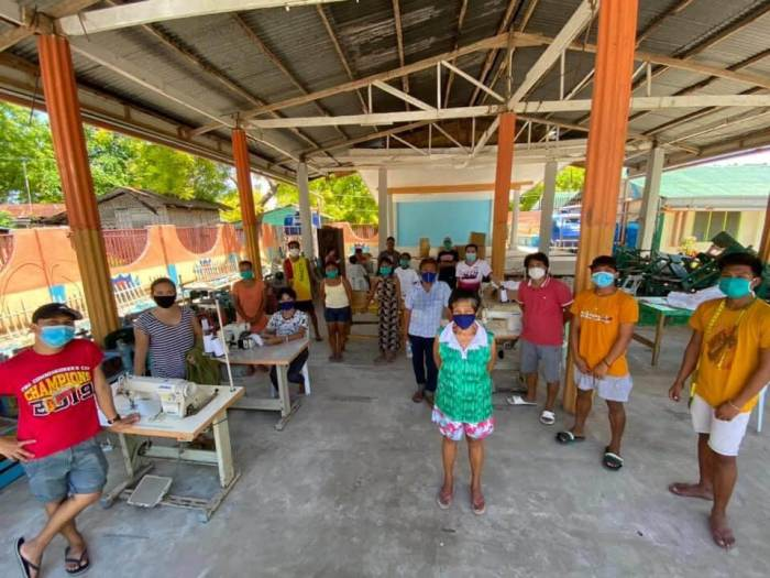 Gilutongan Island residents gathered in their school courtyard to start making masks.