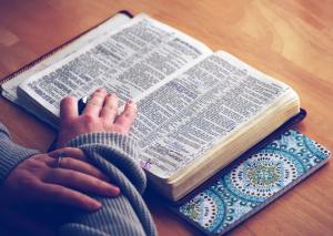 woman's hand on an open bible