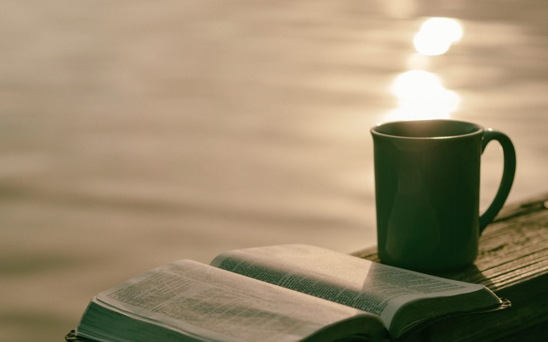 sunrise with coffee mug and bible on a railing water background