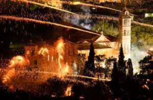 The Panaghia Erithiani Church is hit by rockets from the supporters of the Aghios Marko Church during the Greek celebration of rouketpolemos.