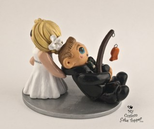 Bride dragging her fishing groom wedding cake topper