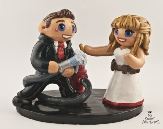 Fireman groom spraying his police bride cake topper