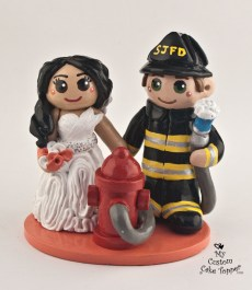 Bride and fireman groom holding hands by fire hydrant cake topper