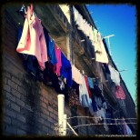 Colorful clothes line a drab grey wall