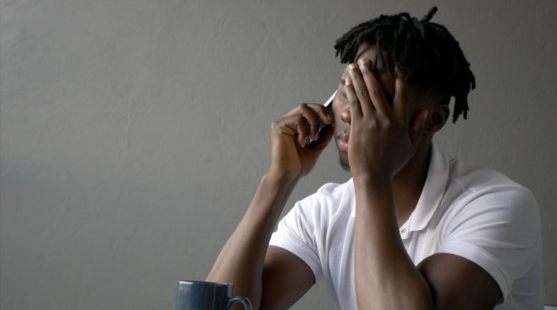 African sad black man talking on a cell phone receiving sad news scaled