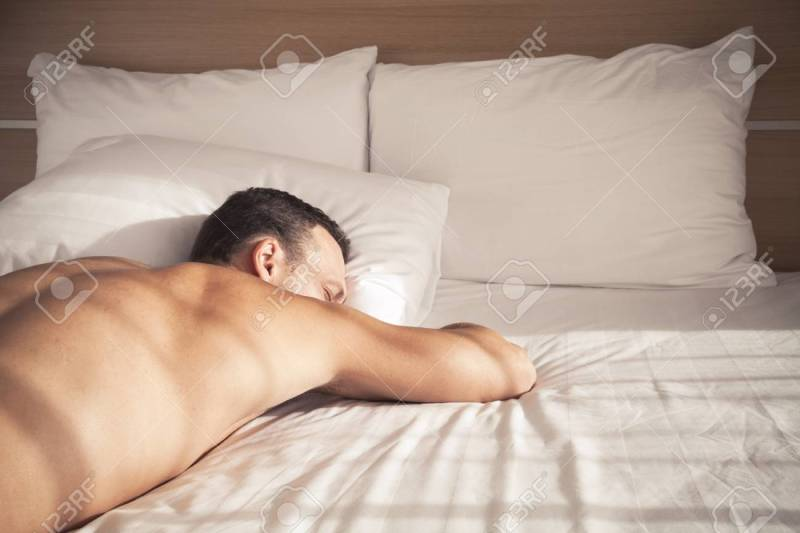 75254408 portrait young european man sleeping in bed on white sheet in morning sunlight 1