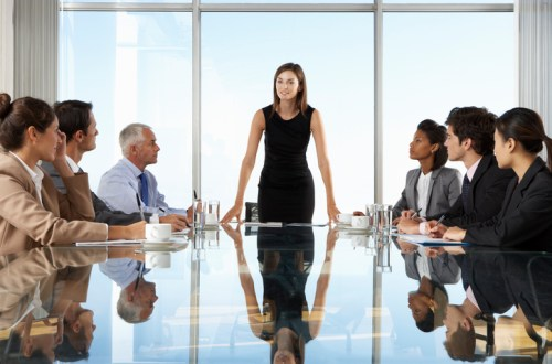 Group Of Business People Having Board Meeting Around Glass