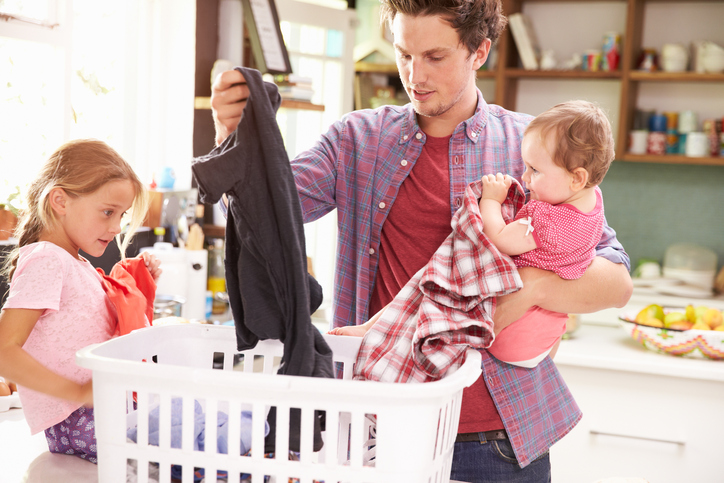 Father And Children Sorting Laundry In Kitchen