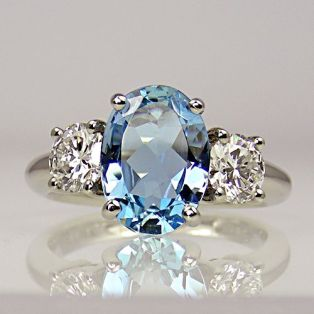 Oval aquamarine with two round brilliant-cut diamonds, one either side, all in claw-collets on platinum shank. Aquamarine weight 1.62 carats. Diamonds total weight 0.82 carats.