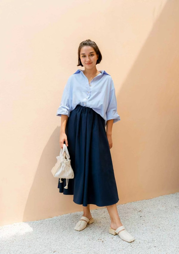 woman with light blue shirt and dark blue skirt holding small bag