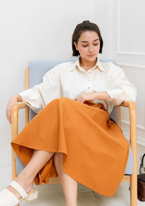 Woman on chair wearing beige cotton shirt with medium sleeves