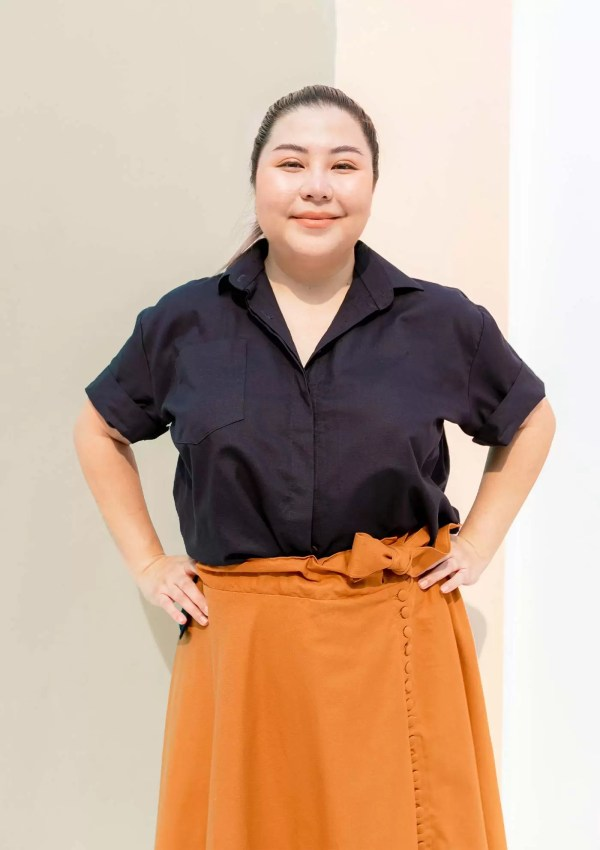 Woman wearing dark blue short sleeve shirt made from organic and recycled cotton