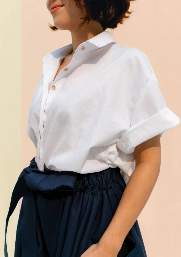 Woman wearing white cotton shirt made from organic and recycled cotton