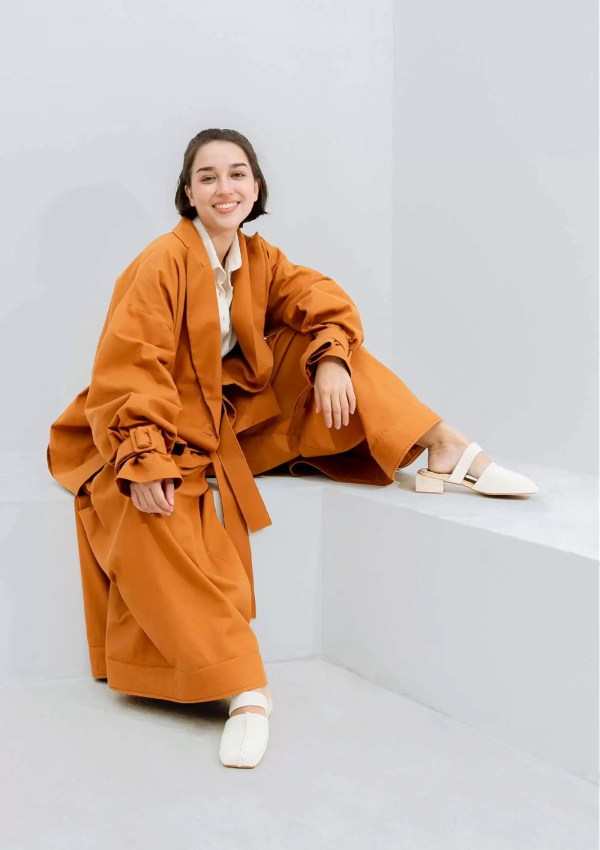 Woman wearing oversized orange trousers made from sustainable materials
