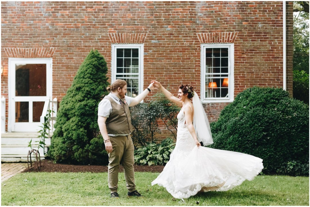 Groom twirling bride in front of brick backdrop at Whitebarn at Middlespring. |Eastern Shore Wedding|