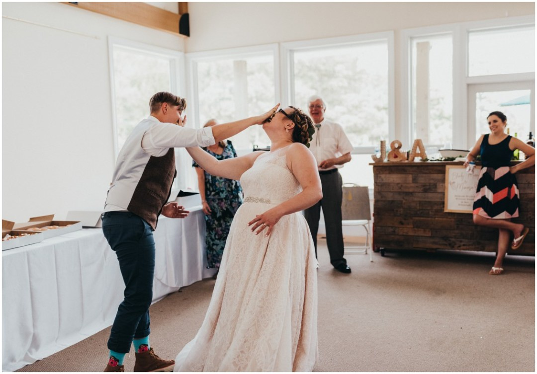 Couple smash donut slices into each other's face. | My Eastern Shore Wedding |