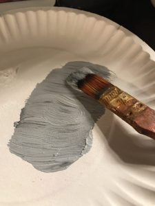 gray paint on a paper plate