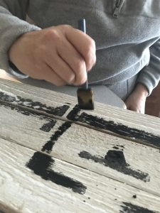painting letters onto pallet wood sign