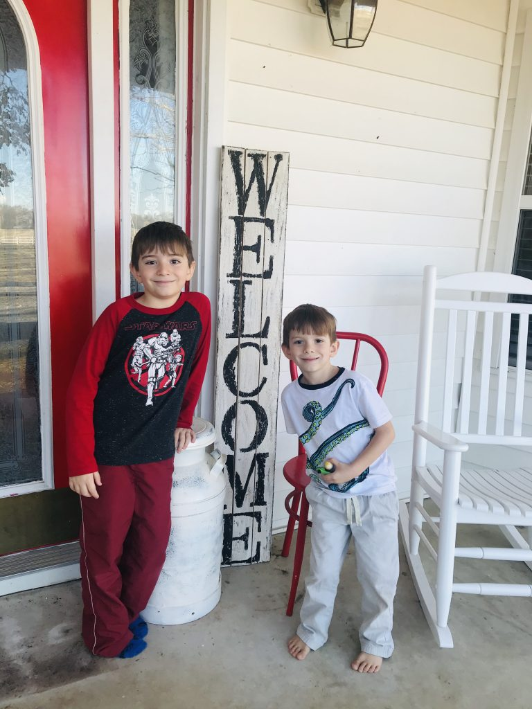 boys with our farmhouse welcome porch sign