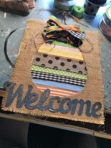 adding a metal welcome to ribbon easter egg cutout canvas