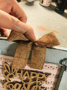 adding burlap bow to painted birds nest frame