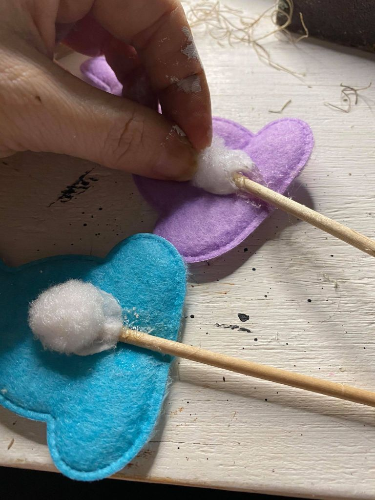 adding wood skewers to fabric bunnies that came from a Dollar Tree headband