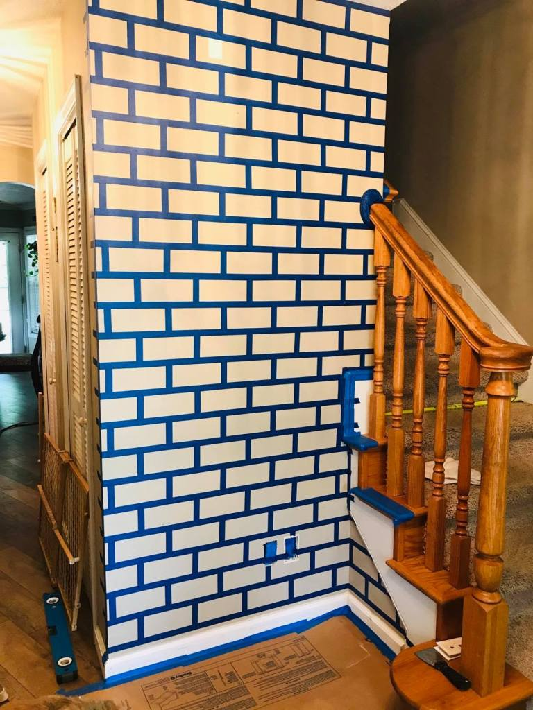 adding painters tape to wall for faux brick design | #fauxbrickwall