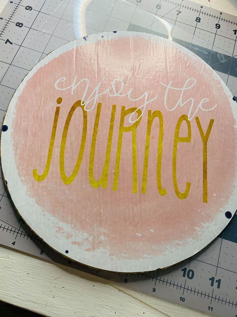 cardboard sign that says enjoy the journey