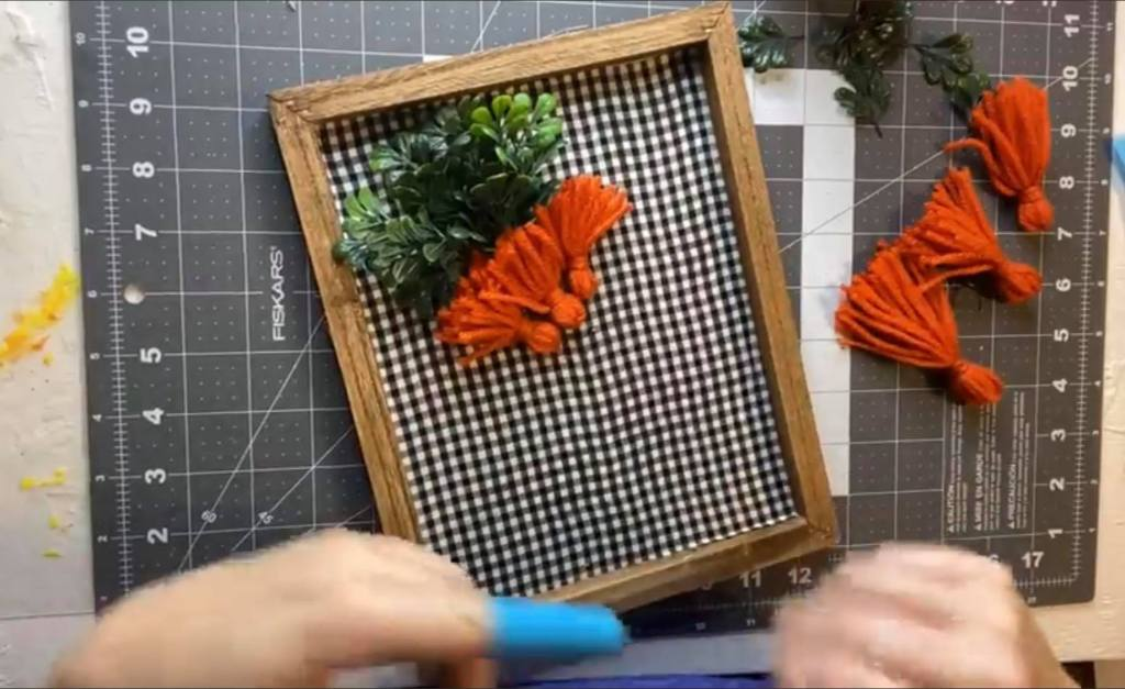 adding orange tassels to a canvas to make a carrot craft