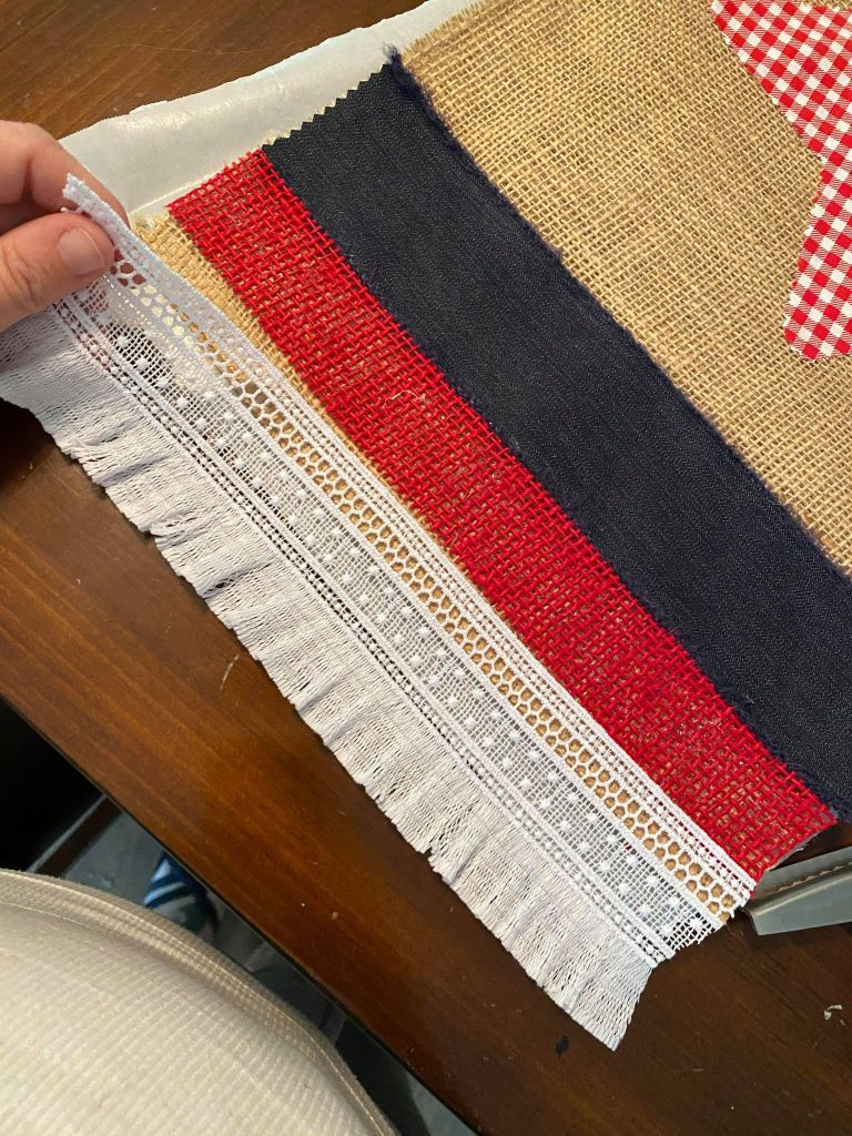 adding a white fringe ribbon to the edge of a burlap table runner