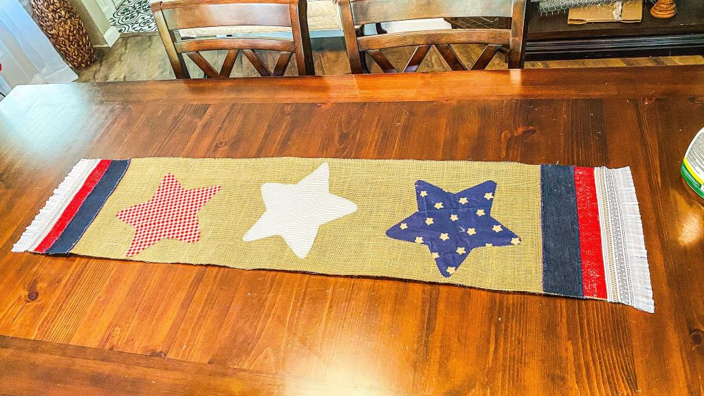 patriotic table runner made with burlap, fabric stars, and ribbon